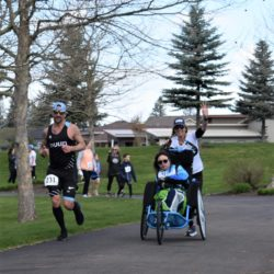 Runner Athletes Racing with Rider Athlete Through Course