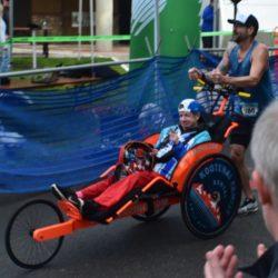 Runner Athlete Pushing Rider Athlete over Finish Line