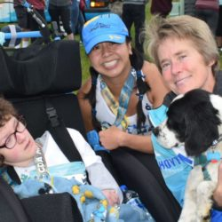 Team President and Female Runner Athlete Posing with Female Rider Athlete and Dog