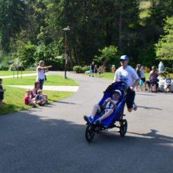 Runner Athlete Pushing Rider Athlete Through Race Course