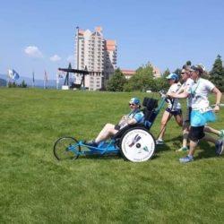 Two Runner Athletes Pushing Rider Athlete