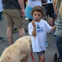 Child Standing Near Dog with Team Hoyt Coeur d'Alene Shirt