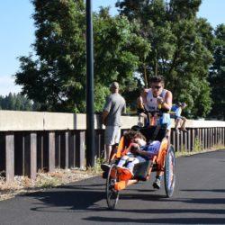 Runner Athlete Pushing Rider Athlete during Triathlon