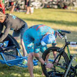Team Member Adjusting Bike Before Race