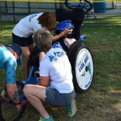 Team Members Assisting Rider Athlete Prepare for Race