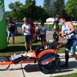 Male Runner Athlete Pushing Female Rider Athlete Through Race
