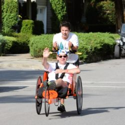 Rider Athlete Waving While Being Pushed by Runner Athlete During Race