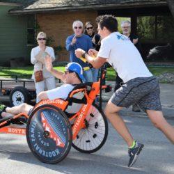 Male Runner Athlete Pushing Rider Athlete During Race