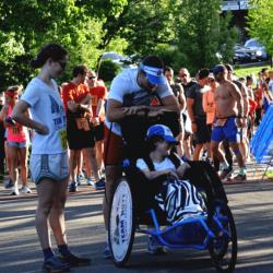 Two Runner Athletes Surrounding Rider Athlete Awaiting Race Start